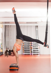 pretty young woman doing pilates exercises with a hanging band