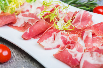 Slices of tasty traditional spanish ham iberico on a white plate