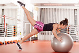 pretty young woman doing pilates exercises with ball