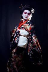 Young beautiful asian woman's portrait, geisha in kimono on blac