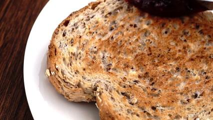 Strawberry raspberry jam being spread on multi-grain toast
