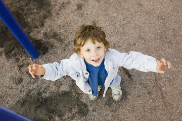 little cute boy playing on playground, hanging on gymnastic ring