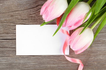 pink tulips and blank card on wooden background