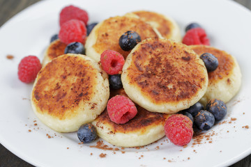 homemade curd fritters on plate with berries