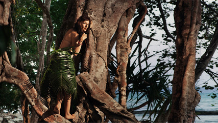 Indigene woman in the palm skirt on the tropical forest and sea