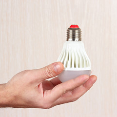 Hand holding a light bulb on a light wood background