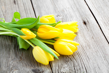 Bouquet of yellow tulips on old wooden boards