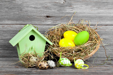 easter decoration with eggs, birdhouse. wooden background