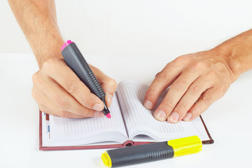Hand written notes in red marker a notepad on a white background