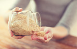 Fototapety close up of female emptying jar with quinoa