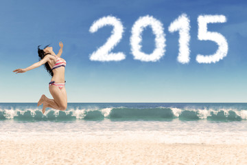 Joyful woman in bikini with numbers 2015