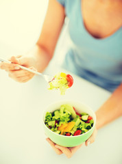 woman eating salad with vegetables