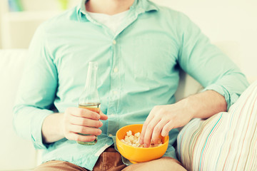 close up of man with popcorn and beer at home