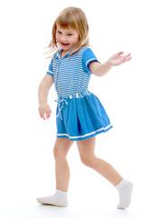 Cheerful girl in a summer short blue dress.