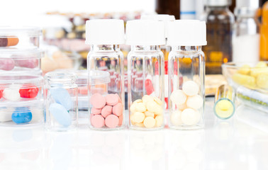 Colorful medical capsules in bottle, on white background