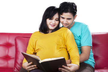 Man read a book with pregnant wife