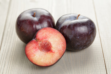 three ripe black plums on wood table