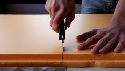 мужчина разрезает ножом лист пенополистирола