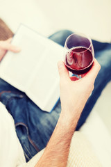 male hand holdind book and glass of red wine