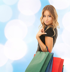 young woman with shopping bags over blue lights