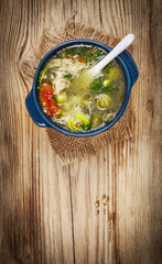 Chicken soup with vegetables on wooden table