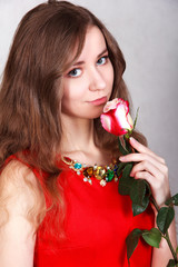 Portrait of a beautiful young woman with a red rose