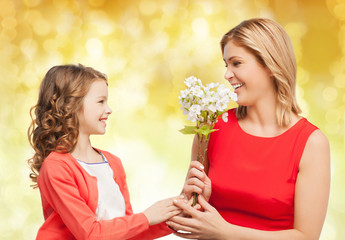 happy little daughter giving flowers to her mother