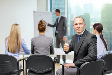 businessman with team showing thumbs up in office