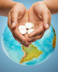cupped hands holding euro coins over earth globe