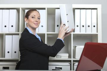 Sekretärin nimmt Akte aus dem Schrank