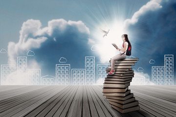Student sitting on a stack of books
