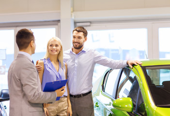 happy couple with car dealer in auto show or salon