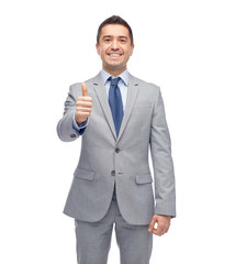 happy businessman in suit showing thumbs up