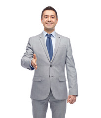 happy smiling businessman in suit shaking hand