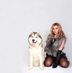 Portrait of a young attractive woman with a husky dog