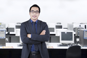 Successful young employee standing in office