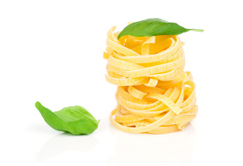 Italian pasta fettuccine nest with basil leaf, isolated on white