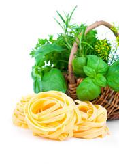 Italian pasta fettuccine nest with wicker basket green herbs, on