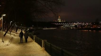 Evening quay in winter, veiw of University, people go