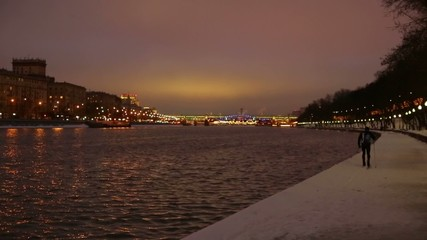 Townsman skiing on the waterfront in the evening in winter city