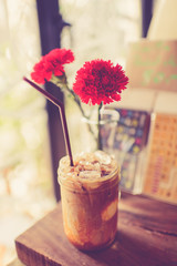 Vintage Ice coffee cup on grunge wooden table, dept of field.