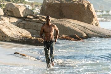 Topless, muscular black man running on beach