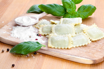 Homemade pasta ravioli with fresh basil, isolated over wooden ba