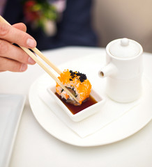 Male hand with Sushi (California Roll) on a white background