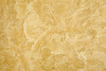 Decorative golden plaster texture on the wall - background