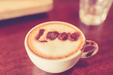 Love message on coffee cup on wooden background with vintage col