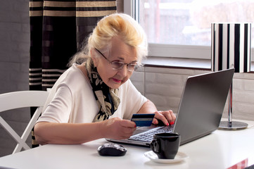 elderly lady makes a purchase through the Internet with a credit