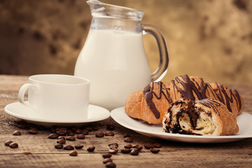 Breakfast with coffee, milk and croissants on wooden table