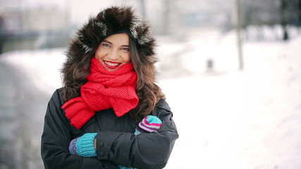 Beautiful woman standing in the snowy park and smiling to camera