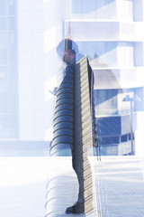 Double exposure of man looking at smartphone and cityscape